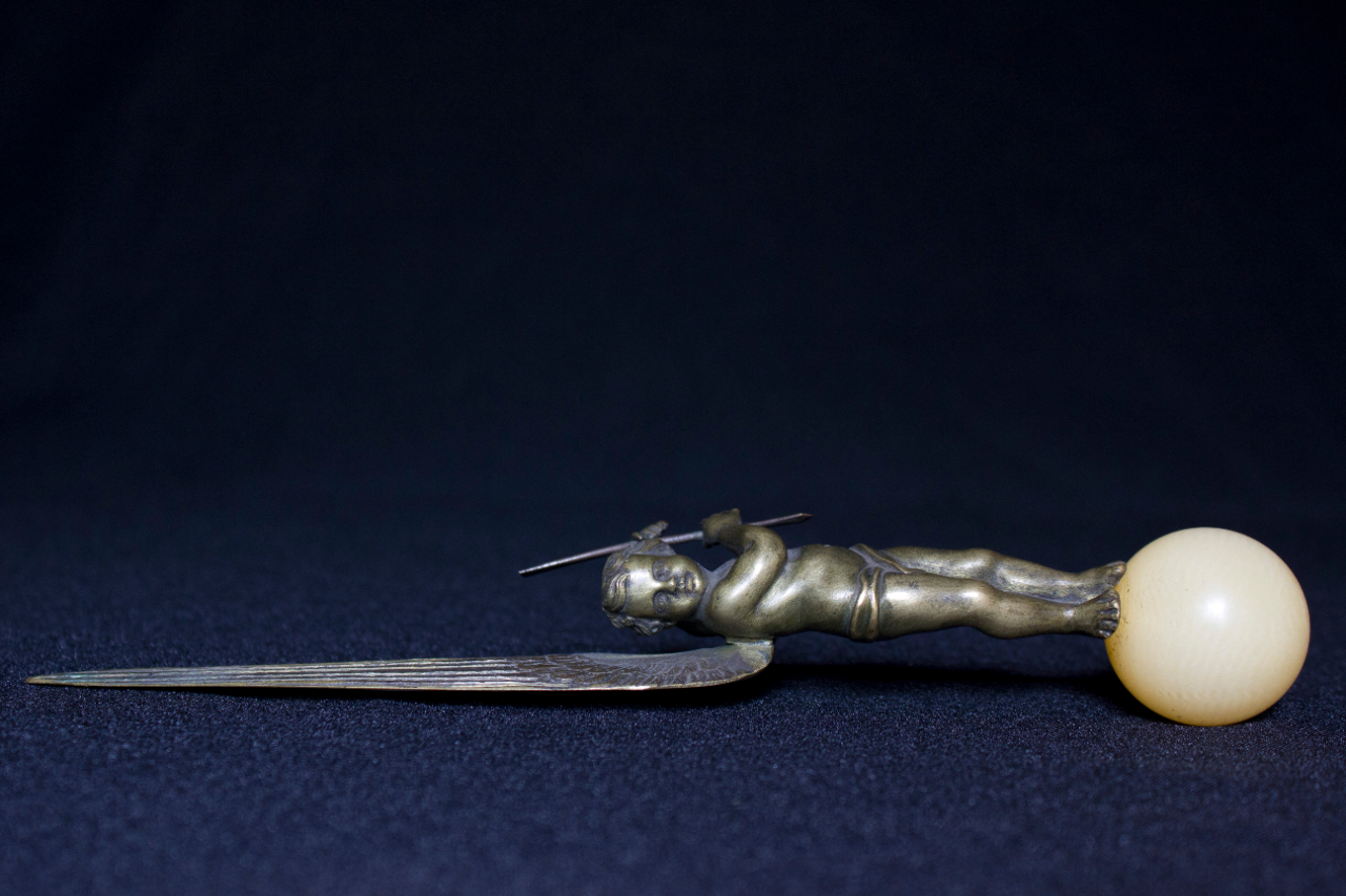 Stylish letter opener of Rossini: a putto in bronze on a natural stone sphere. FEM-866.